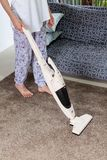 Young woman using a vacuum cleaner while cleaning carpet in the house stock image