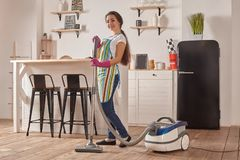 Young woman using vacuum cleaner in home kitchen floor, doing cleaning duties and chores, meticulous interior. Young woman using vacuum cleaner in kitchen room stock images
