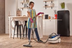 Young woman using vacuum cleaner in home kitchen floor, doing cleaning duties and chores, meticulous interior. Young woman using vacuum cleaner in kitchen room stock photos