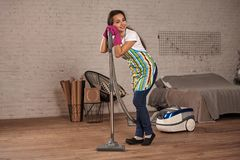 Young woman using vacuum cleaner in home living room floor, doing cleaning duties and chores, meticulous interior. Young female working on house spring stock photos