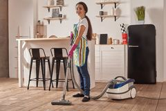 Young woman using vacuum cleaner in home kitchen floor, doing cleaning duties and chores, meticulous interior. Young woman using vacuum cleaner in kitchen room royalty free stock photos