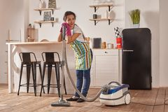 Young woman using vacuum cleaner in home kitchen floor, doing cleaning duties and chores, meticulous interior. Young woman using vacuum cleaner in kitchen room royalty free stock image