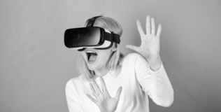 Young woman using a virtual reality headset with conceptual network lines. Funny woman experiencing 3D gadget technology. Close up. Amazed young woman stock photo