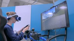 Young woman using virtual reality headset and playing in car drive simulator stock footage