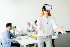 Young woman using virtual reality simulator in the office royalty free stock photo