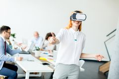 Young woman using virtual reality simulator. Young women using virtual reality simulator during meeting in the office Royalty Free Stock Photos