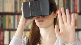 Young woman using VR 360 glasses at home. Seeing something exciting, making gestures with hands. Young woman using VR 360 glasses at home. Seeing something stock footage