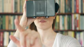 Young woman using VR 360 glasses at home. Seeing something exciting, making gestures with hands stock footage