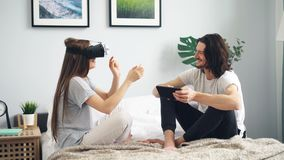 Young woman using vr glasses moving hands while boyfriend touching tablet. Young woman is using virtual reality glasses moving hands while boyfriend is touching stock video footage