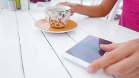 Young woman using white smartphone and drinking stock footage