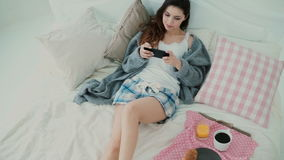 Young woman using wireless technology lying on bed and chatting at home. Girl types on smartphone during breakfast. stock video