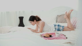 Young woman using wireless technology lying on a white bed and chatting at home. Girl typing on laptop during breakfast. Stock Photos