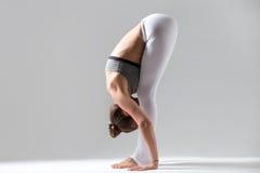 Young woman in uttanasana pose, grey studio background Stock Photo
