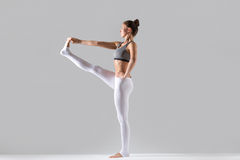Young woman in Utthita Hasta Padangustasana pose, grey studio ba Stock Photography