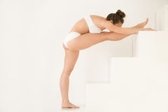 Young woman in Utthita Hasta Padangustasana pose, white color ba. Young attractive woman practicing yoga on stairs, doing Utthita Hasta Padangustasana exercise Royalty Free Stock Photo