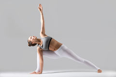Young woman in Utthita parsvakonasana pose, grey studio backgrou. Young attractive woman practicing yoga, standing in Extended Side Angle exercise, Utthita Stock Images
