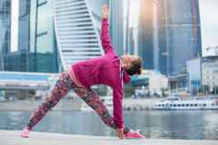 Young woman in Utthita Trikonasana pose against the skyscrapers. Young attractive woman practicing yoga, standing in extended triangle exercise, Utthita Stock Image