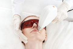 Young woman in uv protective glasses receiving laser skin care on face Stock Photography