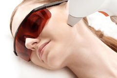 Young woman in uv protective glasses receiving laser skin care on face Royalty Free Stock Image