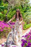 Young woman on vacation biking at flowering garden Royalty Free Stock Image