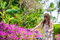 Young woman on vacation biking at flowering garden Stock Photo