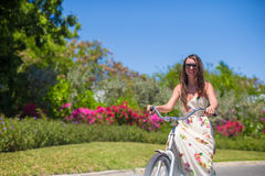 Young woman on vacation biking at lush garden Royalty Free Stock Photos
