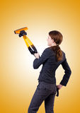 Young woman with vacuum cleaner against gradient Stock Photos