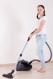 Young woman with vacuum cleaner. Royalty Free Stock Photos