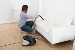 Young woman vacuuming sofa at home Stock Photography