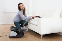 Young Woman Vacuuming Sofa At Home Royalty Free Stock Image