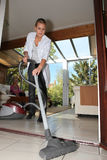 Young woman vacuuming Royalty Free Stock Image
