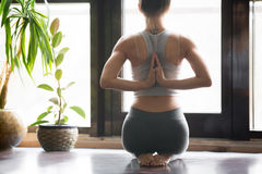 Young woman in vajrasana pose, home interior background, namaste. Young woman practicing yoga with namaste behind the back, sitting in seiza exercise, vajrasana stock photo