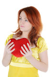 Young woman with valentine's. Young beautiul woman with red heart in her hands on white background. Focus on woman's eyes Stock Photo