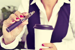 Young woman vaping from an electronic cigarette Stock Images