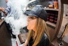 Young woman vaping in restaurant