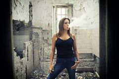 Young woman vaping. Woman vaping in an abandoned House royalty free stock photo