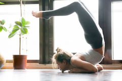 Young woman in variation of vrischikasana pose, home interior Stock Photography