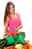 Young woman with variety of grocery products in shopping bag Royalty Free Stock Photo