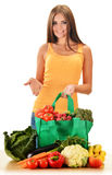 Young woman with variety of grocery products in shopping bag Royalty Free Stock Photos