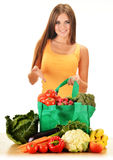 Young woman with variety of grocery products in shopping bag Stock Photos