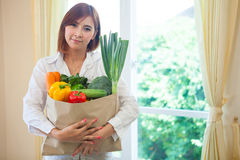 Young Woman with vegetables in shopping bag Stock Photo