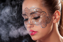 Young woman in a veil of cigarette. Female inhale smoke from cigarette on dark area Royalty Free Stock Images