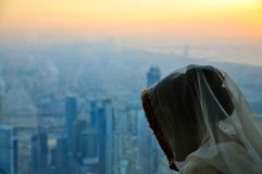 Young Woman in Veil, and View from Burj Khalifa. Young veiled Woman looking down through a Window from the Observation Deck Level of Burj Khalifa, Dubai Royalty Free Stock Photography