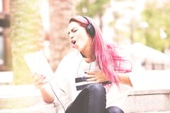 Young woman very excited listening to music on the tablet in the stock photo