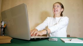 Young woman very quickly typing on a laptop with a facial expression like mad. Heavy work of freelancer. Crazy brunette embodies the idea stock video