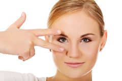 Young woman with victory sign on eye Stock Photos