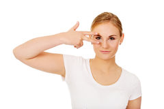 Young woman with victory sign on eye Stock Images