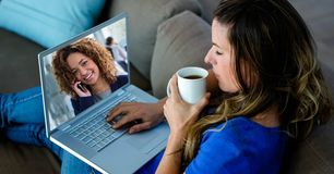 Young woman video conferencing on laptop while having coffee. Digital composite of Young women video conferencing on laptop while having coffee Stock Photo