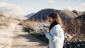 Young woman videographer catching flying aircraft with camera.Controlling landing of drone.Female filmmaker in nature. Using quad copter aircraft to capture royalty free stock images