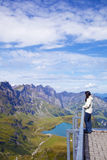 Young woman in a viewpoint of Swiss Alps. Young woman in a viewpoint of Titlis mountain in the Swiss Alps Royalty Free Stock Image